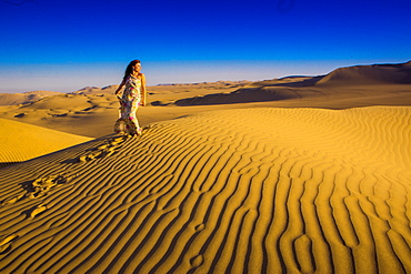 Girl standing on sand dunes at Huacachina Oasis, Peru, South America