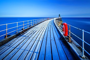 Frost sits on the timbers of Whitby Pier as it extends out to the sea on a cold winters morning, Whitby, North Yorkshire, Yorkshire, England, United Kingdom, Europe
