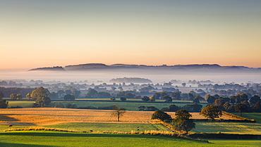 Low autumn morning light rakes across the Cheshire plain with Beeston Castle and the Peckforton sandstone ridge beyond, Cheshire, England, United Kingdom, Europe