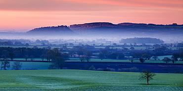 Dawn illuminates Beeston and Peckforton castles on the Peckforton sandstone ridge with mist lying on the Cheshire plain below, Cheshire, England, United Kingdom, Europe