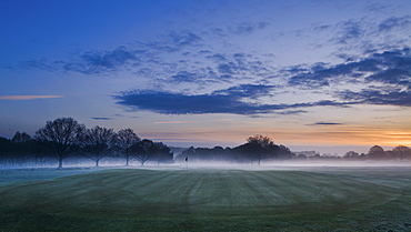 Dawn light seeps across the sky with mist lying across the landscape at Delamere Forest Golf Club, Cheshire, England, United Kingdom, Europe
