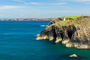 A solitary walker perched high on the cliffs stretching for miles along the Pembrokeshire coast path on a calm summers day, Wales, United Kingdom, Europe