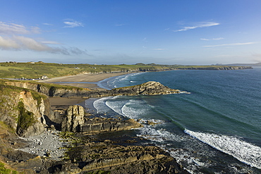 Waves gently roll into Whitesands Bay (Porth Mawr) on a summers evening along the Pembrokeshire coastal path, Wales, United Kingdom, Europe