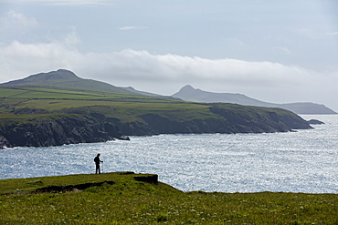 A walker enjoying a moments rest to admire the stunning views from the cliffs along the Pembrokeshire coast path, Wales, United Kingdom, Europe