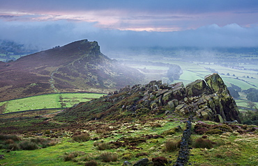Morning mist and fog clear the landscape to reveal Hen Cloud and the gritstone rocks of the Roaches, Peak District, Derbyshire, England, United Kingdom, Europe