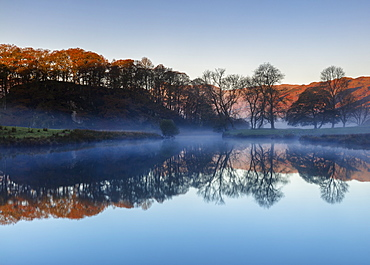 Dawn light reveals the autumn colour of trees and distant fells with mist lying above Elterwater revealing a perfect reflection, Lake District National Park, UNESCO World Heritage Site, Cumbria, England, United Kingdom, Europe