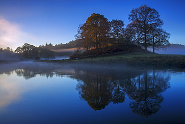 A calm clear autumn morning at Elterwater as the first light of a new day illuminates the trees and mist, Lake District National Park, UNESCO World Heritage Site, Cumbria, England, United Kingdom, Europe