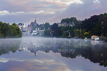 Early morning mist settles on the River Dee with boats and buildings reflected in the still water, Chester, Cheshire, England, United Kingdom, Europe