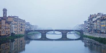 Looking along the Arno River to the Renaissance Ponte Santa Trinita bridge on a misty ethereal morning, Florence, Tuscany, Italy, Europe