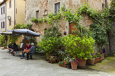 People sitting outside at a restaurant within a small courtyard surrounded by flowers in Pienza, Tuscany, Italy, Europe