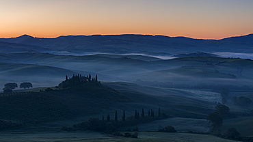 Pre-dawn mist lies in the fields and hills of the Val d'Orcia beyond a farmhouse perched on top of a small outcrop, UNESCO World Heritage Site, Tuscany, Italy, Europe