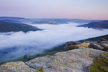 Dawn light breaks above the Peak District hills with a cloud inversion covering the Ladybower Reservoir below Bamford Edge, Peak District, Derbyshire, England, United Kingdom, Europe