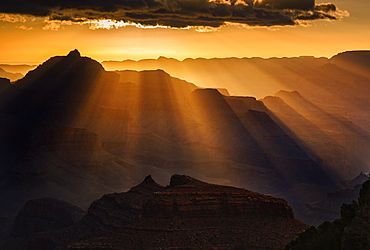 Sun rays extend from a cloud perched on the horizon putting Vishnu temple into silhouette, Grand Canyon National Park, UNESCO World Heritage Site, Arizona, United States of America, North America
