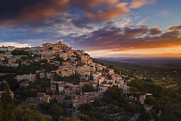 Dawn light illuminates the houses and buildings of Gordes as they spiral up around the rock plateau high above the Luberon, Vaucluse, Provence, France, Europe
