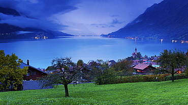 Looking over the chalets and church of Brienz to Lake Brienz as twilight falls over the Bernese Oberland, Switzerland, Europe