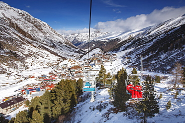 Looking down on the village of Obergurgl sat at the top of the Otztal valley as skiers ascend the mountain on chairlifts, Tyrol, Austrian Alps, Austria, Europe