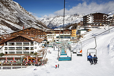 The alpine skiing village of Obergurgl with skiers relaxing while others head off on chairlifts to runs in the Otztal Alps, Tyrol, Austria, Europe