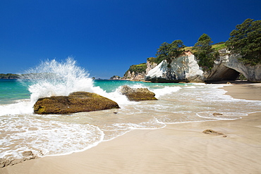 Waves splashing against large rocks on the beach in Cathedral Cove, Coromandel, Waikato, North Island, New Zealand, Pacific