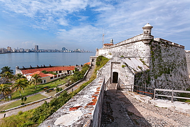 Looking across the calm waters of Havana Bay to Havana with the 16th century fortress, Morro Castle, standing guard, Havana, Cuba, West Indies, Caribbean, Central America