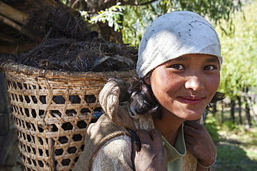 A Bhutanese girl carries fodder to feed her livestock in a village near Paro, Bhutan, Asia