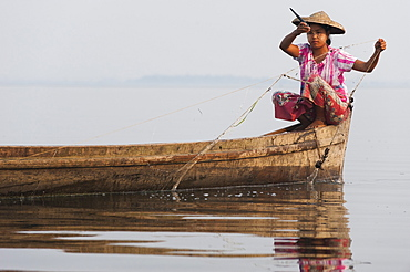 A young woman pulls in her nets at the end of the day on Indawgyi Lake, Kachin State, Myanmar (Burma), Asia