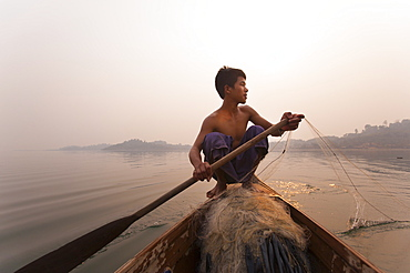 A young man pulls in his nets at the end of the day on Indawgyi Lake, Kachin State, Myanmar (Burma), Asia