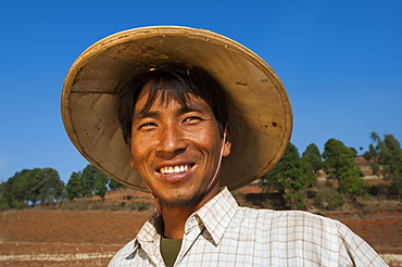 A man takes a short break from harvesting wheat to smile for the camera, Shan State, Myanmar (Burma), Asia