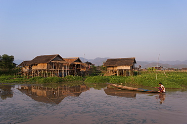 A man paddles his canoe past one of the floating villages on Inle Lake, Myanmar (Burma), Asia