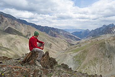 A trekker stops to admire the views from the top of the Konze La in the remote Himalayan region of Ladakh in northern India, India, Asia