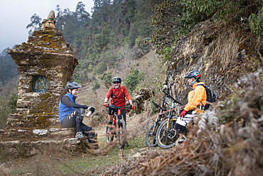 Mountain bikers take a break near a moss covered Tibetan chorten in the Himalayas in the Gosainkund region, Nepal, Asia