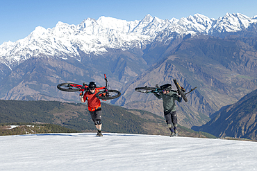 Mountain bikers carry their bikes up a snow covered slope in the Himalayas with views of the Langtang range in the distance, Nepal, Asia
