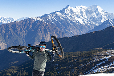 A mountain biker carries his bike up in the Himalayas with views of the Langtang range in the distance, Nepal, Asia