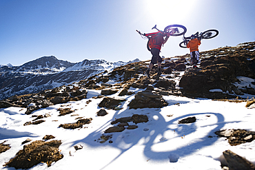 Mountain bikers carry their bikes up a snow covered hillside in the Nepal Himalayas with views of the Langtang mountain range, Nepal, Asia