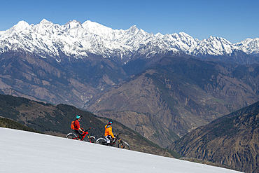 Mountain biking on a snow covered slope in the Himalayas with views of the Langtang mountain range in the distance, Nepal, Asia
