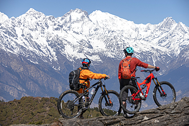 Mountain biking in the Himalayas with views of the Langtang mountain range in the distance, Nepal, Asia