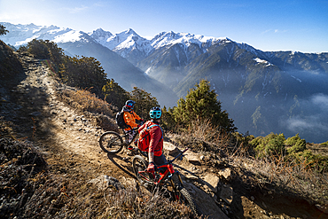 Mountain bikers take a rest on an Enduro style single track trail in the Nepal Himalayas near the Langtang region, Nepal, Asia
