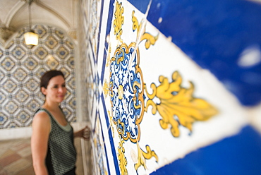 A woman admires beautuful Azelejo tiles on display at The National Azulejo Museum in Lisbon, Portugal, Europe