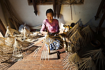 A woman makes umbrellas from bamboo using a traditional method in Shan State, Myanmar (Burma), Asia