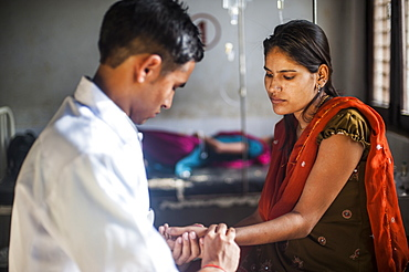 A doctor takes a woman's pulse pressure in a hospital in Nepal, Asia