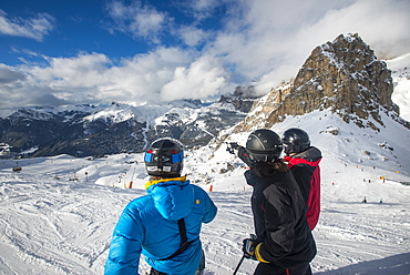 Skiers look at the Dolomites while skiing at Campitello di Fassa, Trentino, Italy, Europe