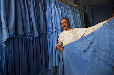 A shopkeeper demonstrates that not all burqas are identical, Herat, Afghanistan, Asia