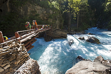Hikers crossing a wooden bridge between Chhepka and Amchi Hospital in Dolpa, a remote region of Nepal, Himalayas, Nepal, Asia