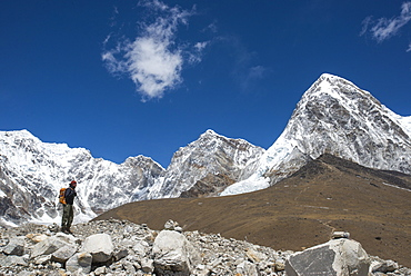 A trekker in the Everest region on the way up to Everest Base Camp, a view of Pumori in the distance, Khumbu Region, Himalayas, Nepal, Asia