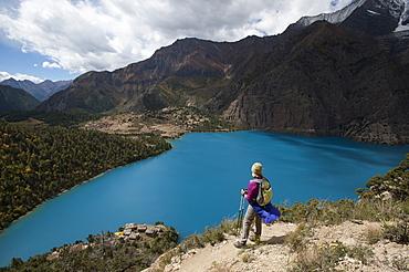 A trekker stands above the turquoise blue Phoksundo Lake in the Dolpa region, Himalayas, Nepal, Asia