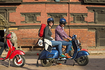 A tourist on a scooter outside a Newari building in Patan in Kathmandu, Nepal, Asia