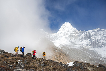 A team of four climbers make their way to Ama Dablam Base Camp, the 6856m peak seen in the distance, Khumbu Region, Himalayas, Nepal, Asia