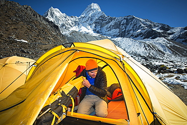A mountaineer packs his bag in preparation to climb Ama Dablam, the 6856m peak in the distance, Khumbu Region, Himalayas, Nepal, Asia