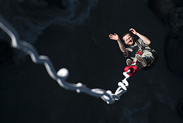 A man smiles for the camera as he is bounced back up during a Bungee jump at The Last Resort, Nepal, Asia