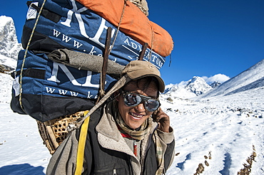 A Sherpa near Dingboche hauling gear to Everest Base Camp for the climbing expeditions stops for a quick rest, Khumbu Region, Nepal, Asia