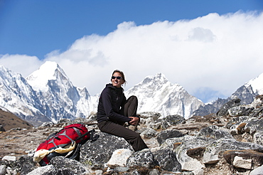 A trekker on her way to Everest Base Camp stops to take in the views, Khumbu Region, Himalayas, Nepal, Asia